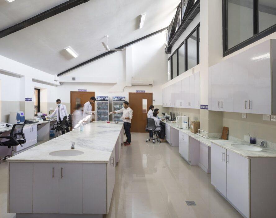 espace de laboratoire médical avec une longue île avec des comptoirs en marbre