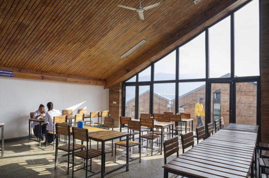coin repas avec petites tables et chaises en bois et un mur de verre