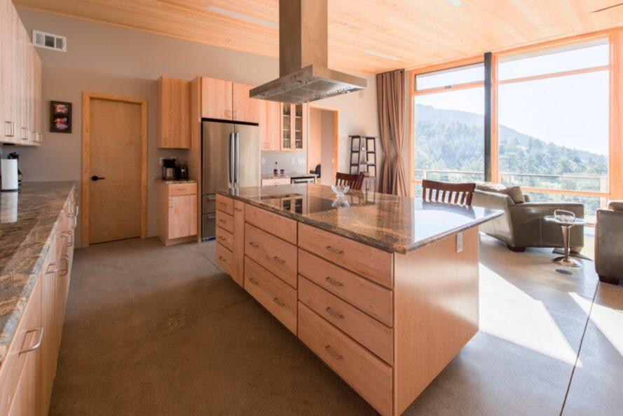 grand îlot de cuisine en bois dans une pièce avec un mur de verre