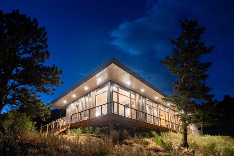 maison en verre et en acier avec toit incliné tout éclairé de l'intérieur la nuit