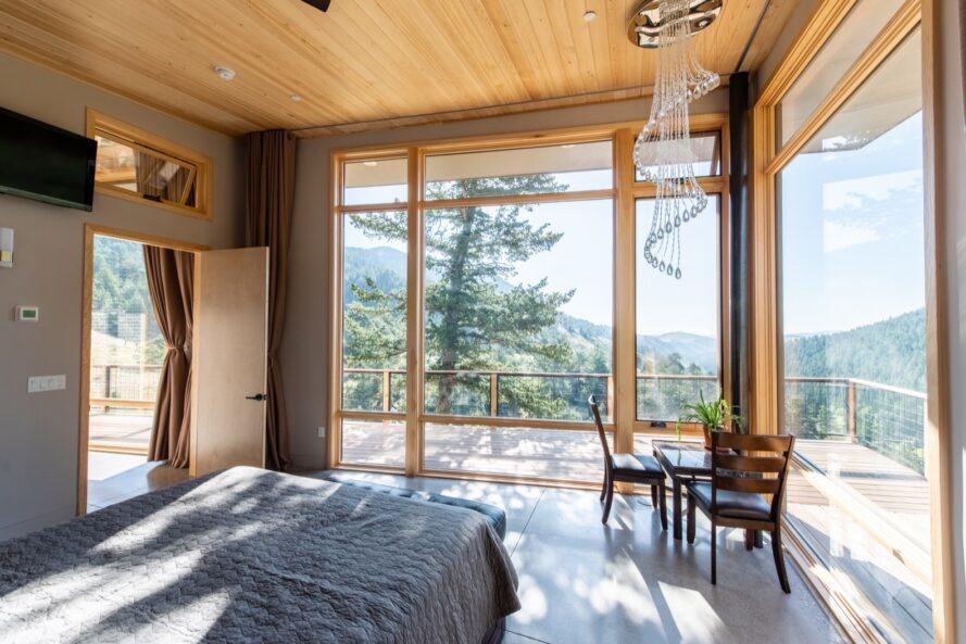 lit et petit ensemble de salle à manger dans une pièce avec deux murs en verre