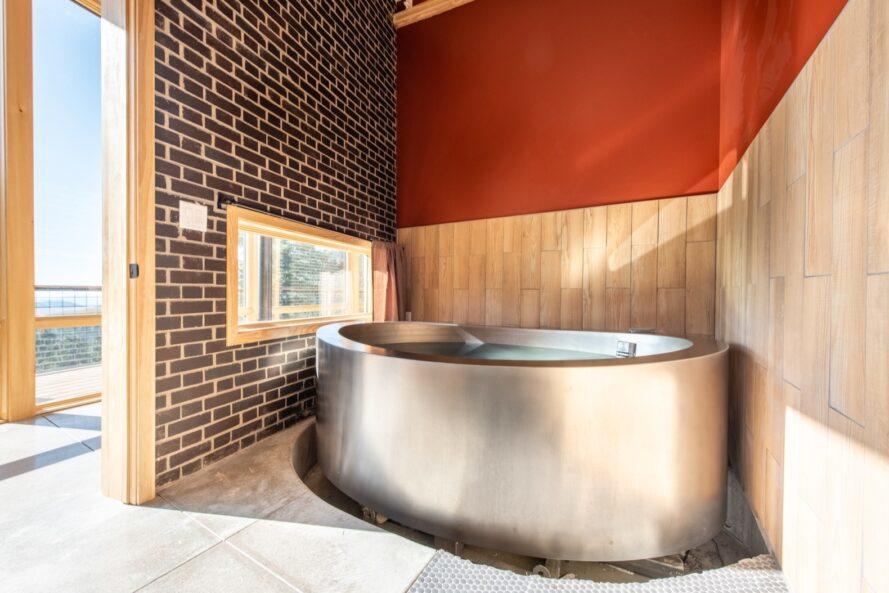 grande baignoire en acier à côté d'un mur de briques