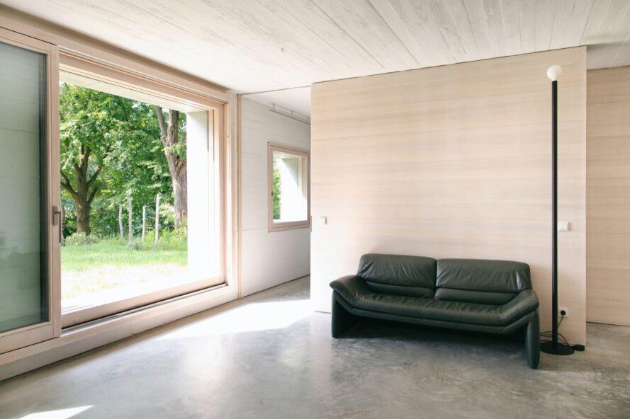 canapé foncé contre un mur en bois clair