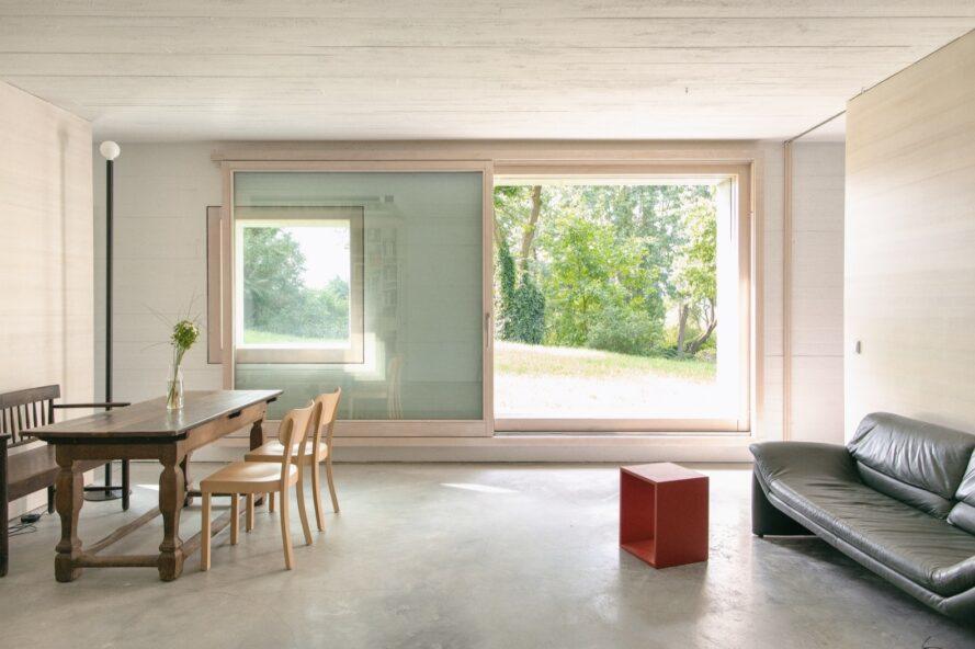 canapé foncé et table à manger en bois en bois avec des murs en bois clair et de grandes fenêtres