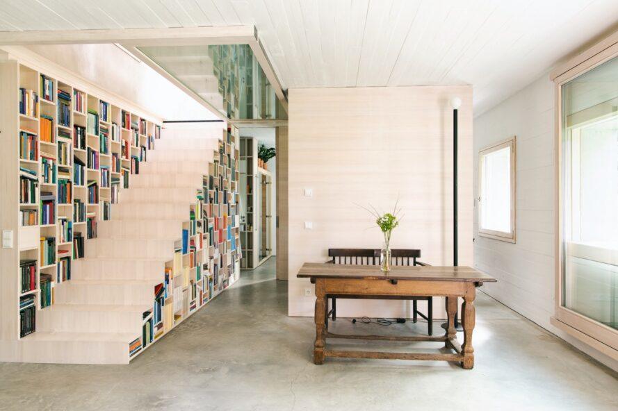 table à manger à côté des escaliers qui se double d'une bibliothèque