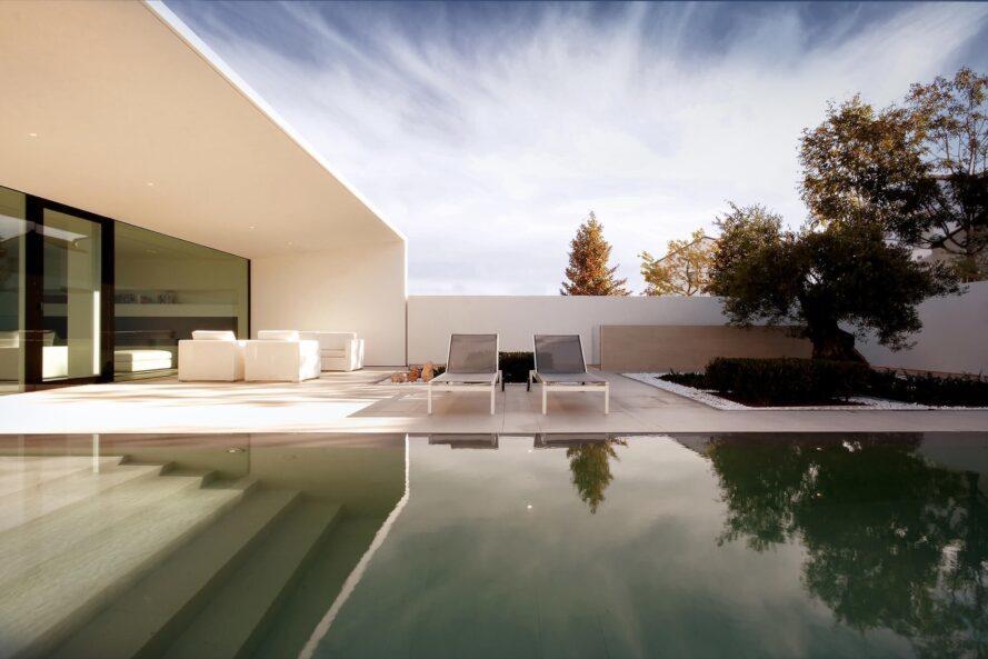 piscine en premier plan et chaises longues sur un patio en arrière-plan