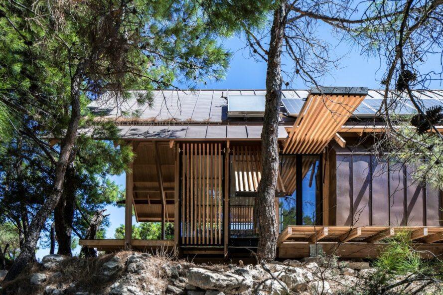 maison sur paysage rocheux avec panneaux ouverts
