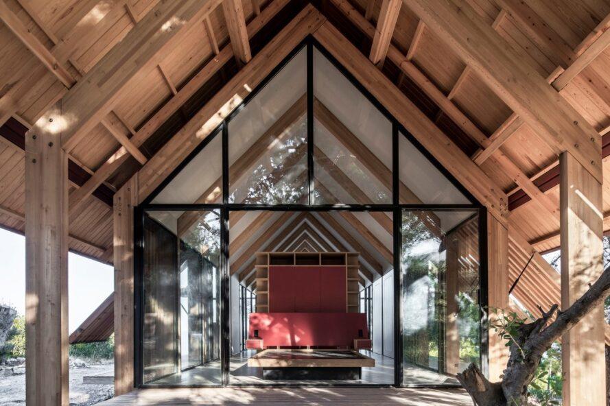intérieur de la maison avec grand plafond voûté et façade entièrement vitrée