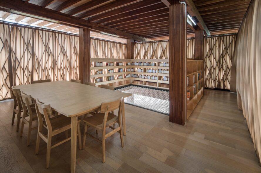 intérieur d'une bibliothèque en bois avec étagères, tables et chaises