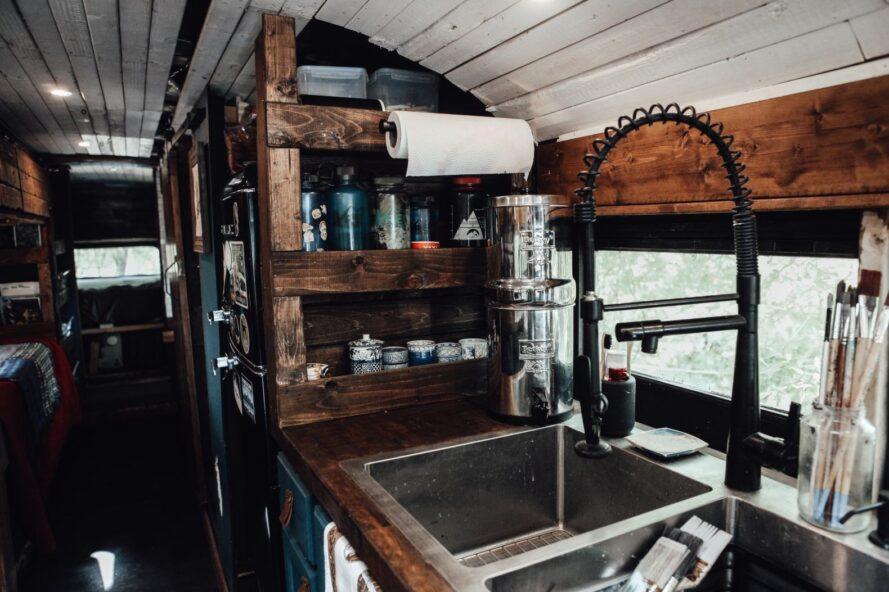 une cuisine avec des étagères en bois à côté d'un grand évier