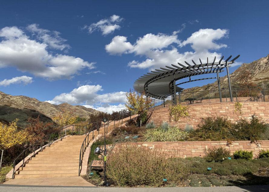 un escalier extérieur incurvé menant à un pavillon. la zone environnante est pleine de plantes vertes et jaunes