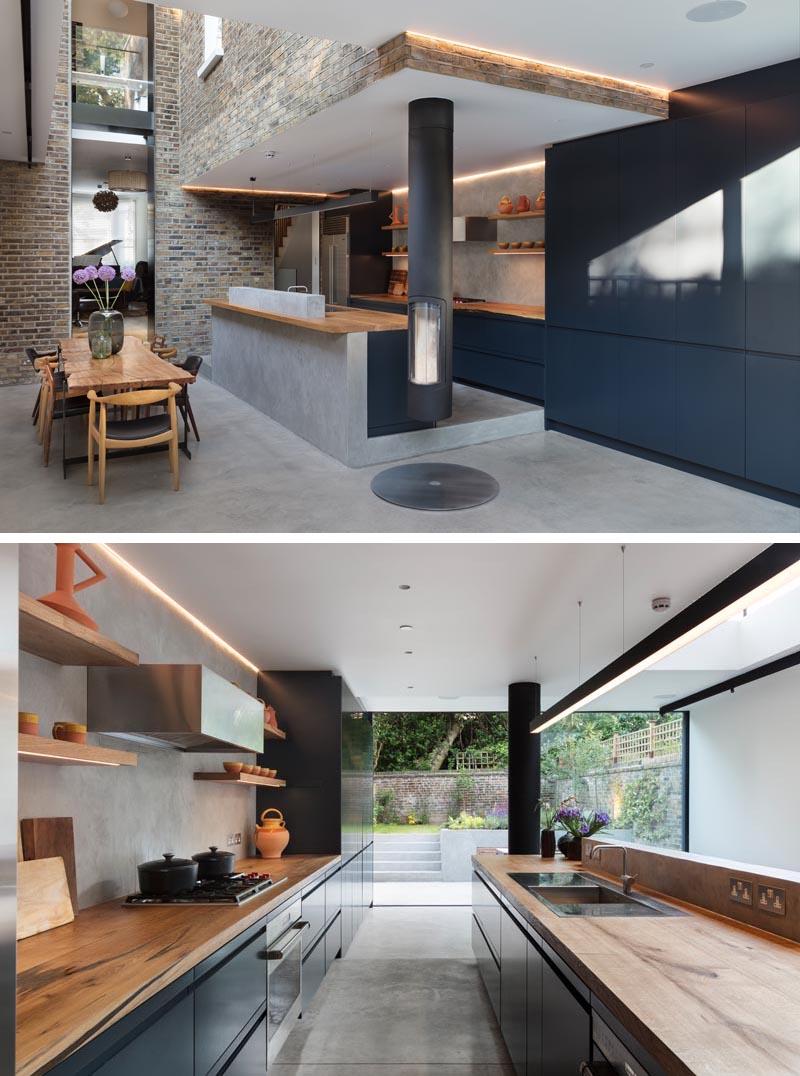 Conçue dans un esprit ludique, cette extension de maison moderne a permis la création d'un espace de vie, d'un coin repas et d'une cuisine moderne légèrement surélevée avec des armoires sombres, des sols en béton et des comptoirs en chêne. #DarkKitchen #WoodCountertop #ConcreteFloor #DarkCabinets #KitchenDesign
