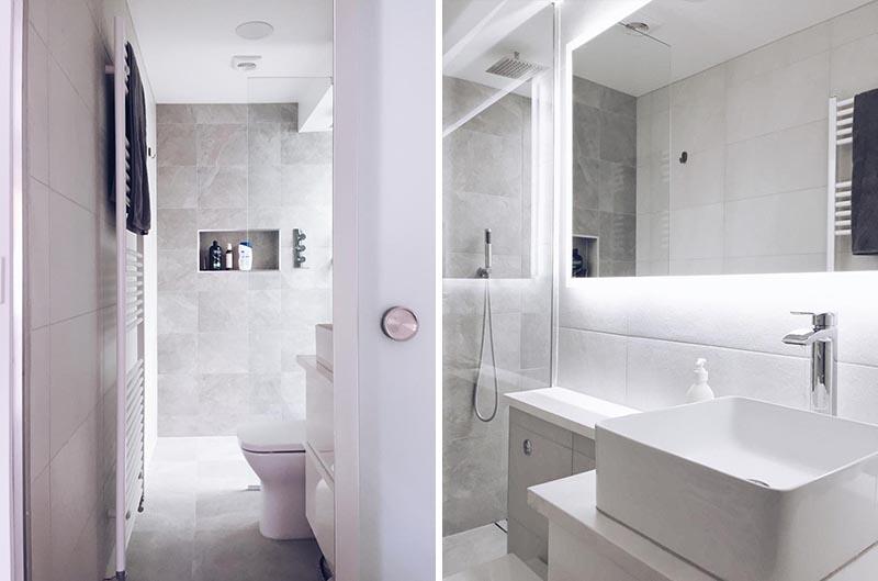 Cette salle de bains privative moderne dispose d'une douche à l'italienne avec une niche de douche intégrée et un miroir rétro-éclairé est monté au-dessus de la vanité. #BacklitMirror #ModernBathroom #ShowerNiche