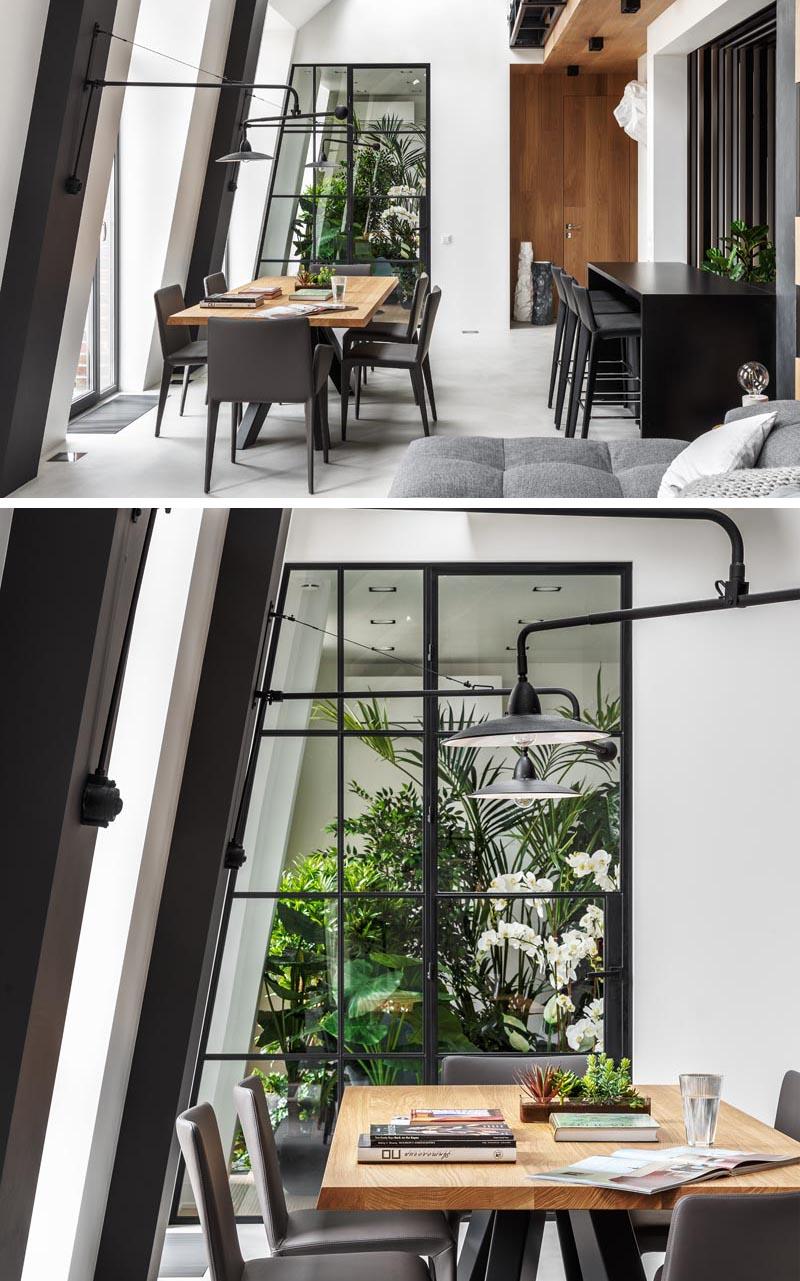 Cet appartement moderne dispose d'une salle des plantes intérieure qui peut être vue à travers un mur de verre à cadre noir, avec une porte qui s'ouvre pour révéler un coin salon calme et paisible. #IndoorGarden #IndoorPlantRoom #IndoorGardenRoom #ReadingNook #InteriorDesign
