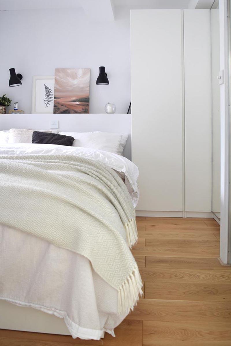 Dans cette chambre moderne, de grands placards utilisent l'espace à côté du lit, tandis qu'une étagère intégrée permet l'affichage d'art et de décoration. #BedroomDesign #ModernBedroom