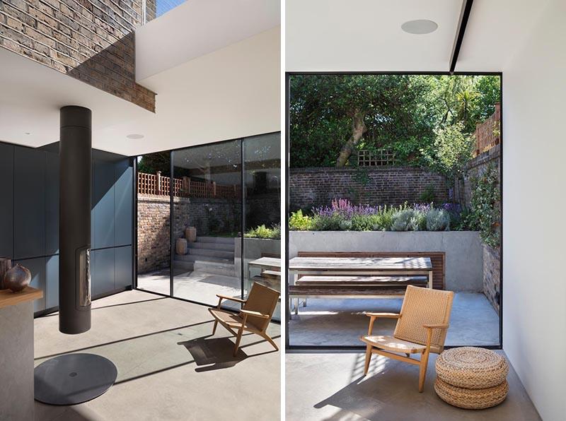Cette extension de maison en verre moderne dispose d'un foyer pivotant, tandis que les portes coulissantes du sol au plafond donnent accès au patio et au jardin isolé surélevé. #PivotingFireplace #FireplaceIdeas #Patio #Garden #SlidingDoors