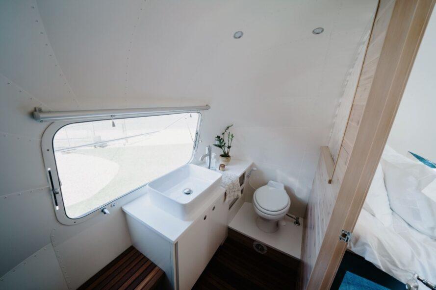 salle de bain avec lavabo blanc et une petite fenêtre