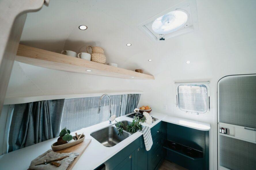 cuisine compacte avec comptoir blanc et étagères ouvertes