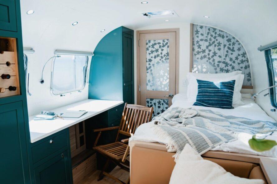 lit blanc à côté d'un petit bureau blanc à l'intérieur d'un Airstream