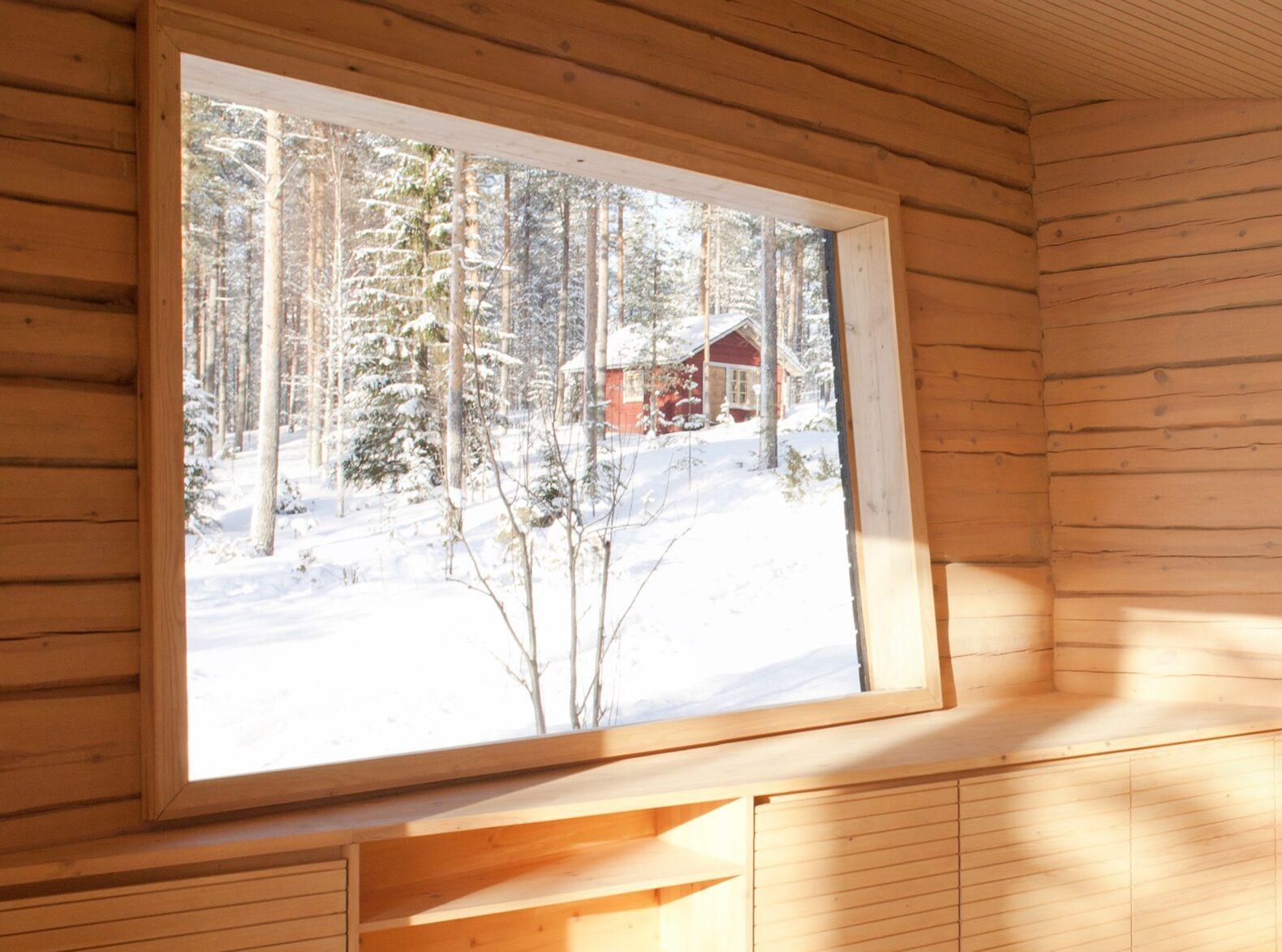 Intérieur d'un bâtiment en bois avec une fenêtre qui donne sur une forêt enneigée