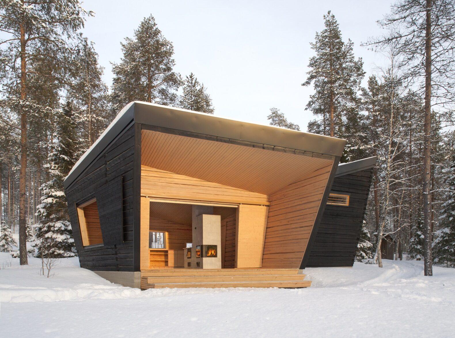 un bâtiment angulaire avec une façade en bois noir, des accents de bois clair et une entrée ouverte au milieu d'une forêt enneigée