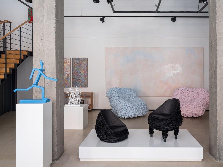 une exposition de la galerie avec une statue bleue humaine à gauche et deux chaises noires au centre de l'exposition