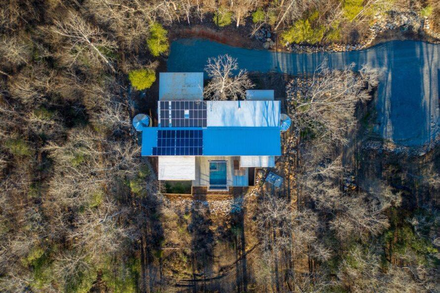 vue aérienne de panneaux solaires toit couvert d'une maison entourée d'arbres
