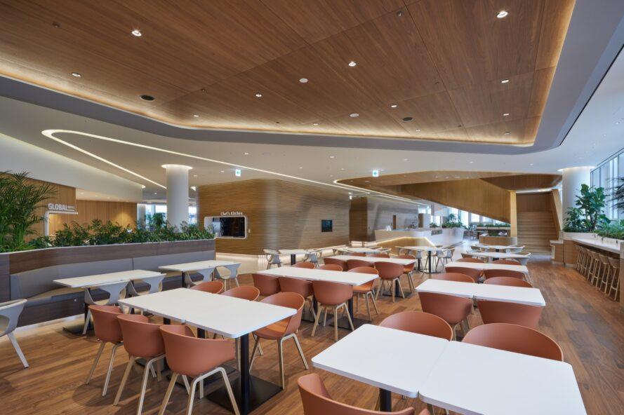tables blanches avec des chaises orange dans une grande pièce ouverte avec des plafonds en bois