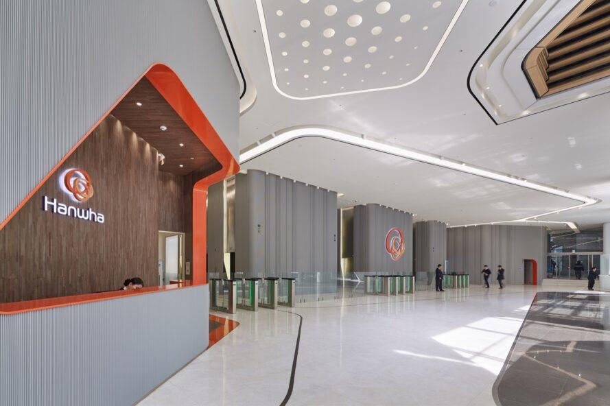 grande salle blanche avec des accents de bois et d'orange