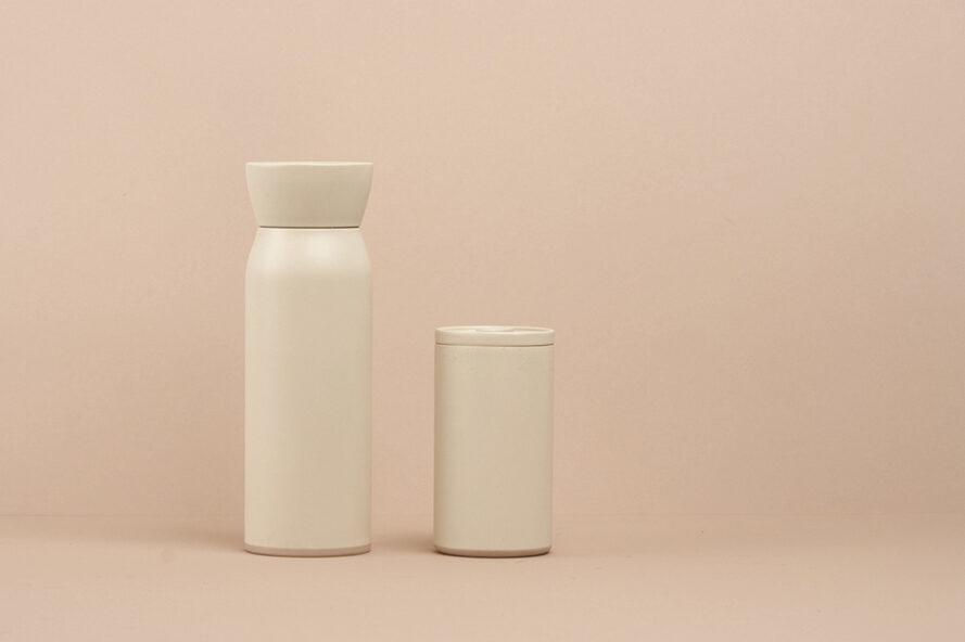 Bouteille d'eau blanche et tasse de café réutilisable blanche sur fond rose
