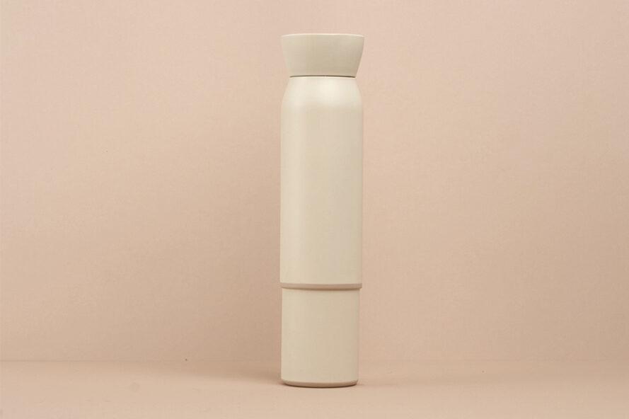 Bouteille d'eau réutilisable blanche empilée sur une petite tasse à café blanche
