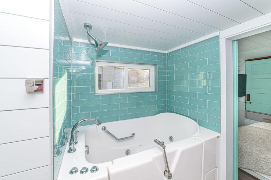 bain à remous avec des murs carrelés turquoise