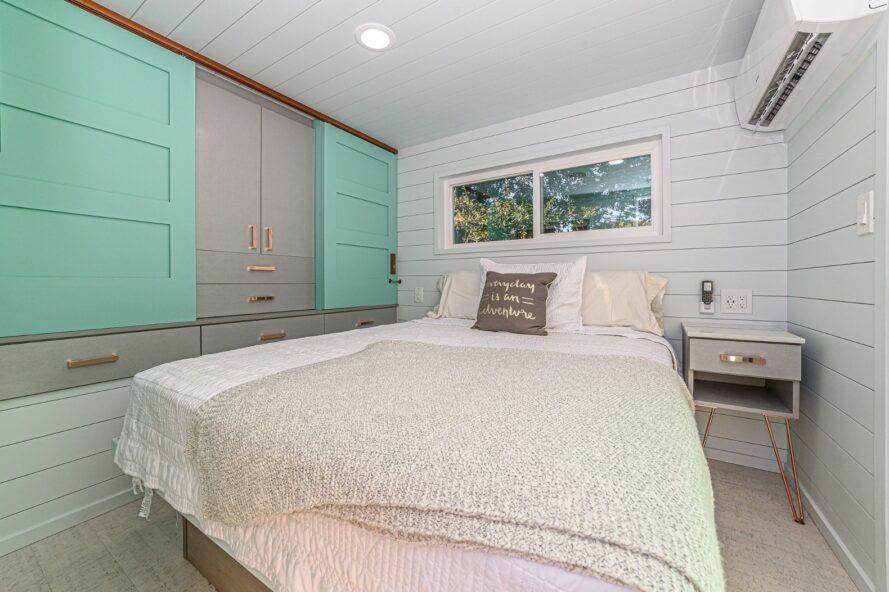 lit blanc à côté d'un placard de rangement gris et turquoise