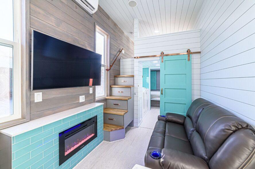 canapé gris face à une petite cheminée numérique et télévision murale à écran plat