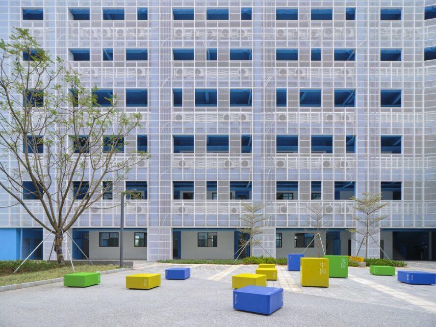 un bâtiment scolaire avec une cour devant. des sièges bleus, jaunes et verts sont placés dans toute la cour