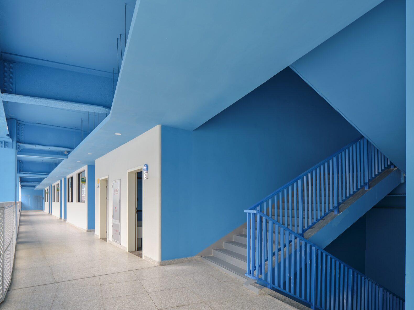 couloir intérieur d'une école aux murs et plafonds bleus