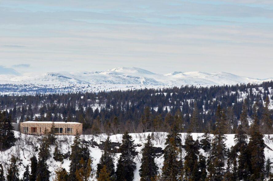 cabane en bois sur un paysage enneigé et montagneux