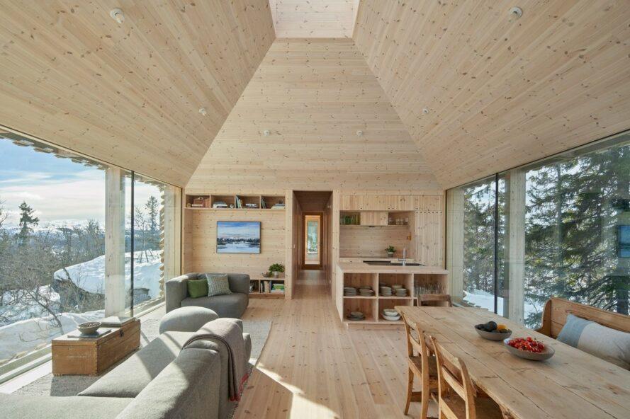 intérieur de la cabine en bois avec plafond à double hauteur, canapés gris et table à manger en bois