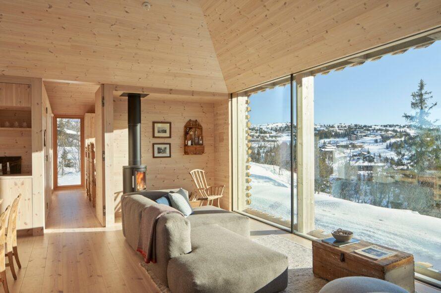 canapés gris et poêle à bois près du mur de verre révélant une vue sur la montagne