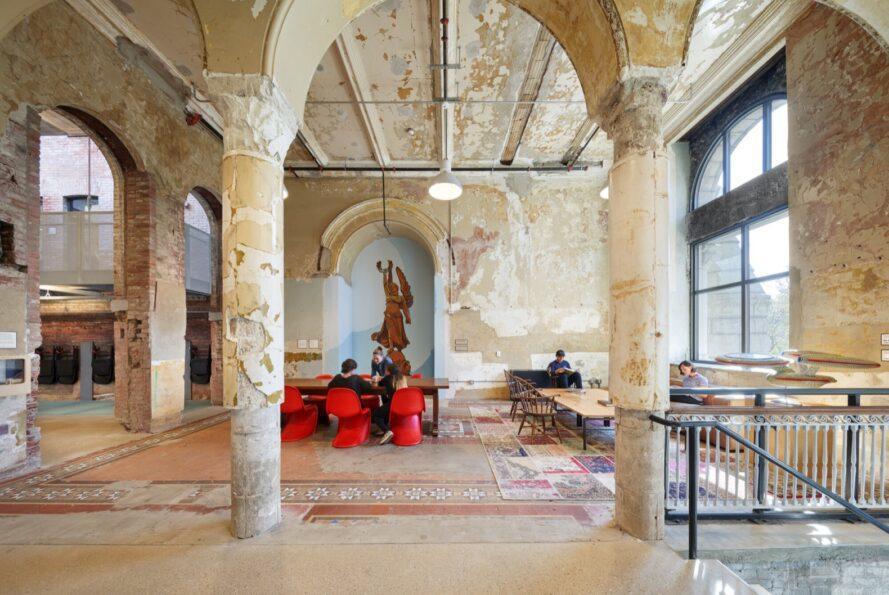 tables en bois et chaises rouges dans une pièce avec du papier peint écaillé et de grandes colonnes