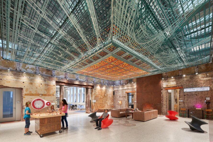canapés bruns et chaises tournantes dans une salle de musée avec un plafond métallique