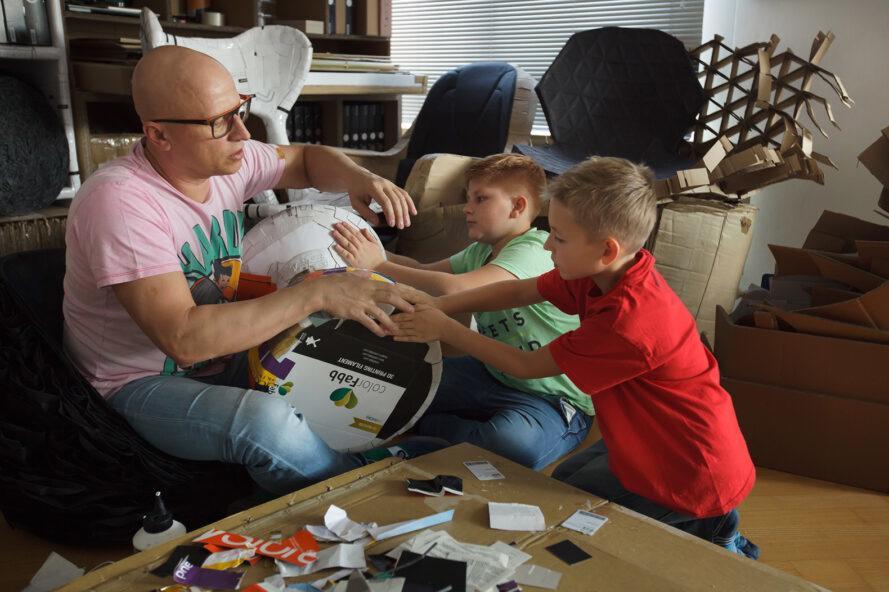 un homme et deux enfants travaillant ensemble sur un meuble en papier