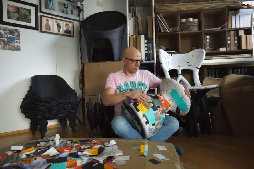 un homme en chemise rose entouré de papier coloré alors qu'il travaille à la création d'un meuble
