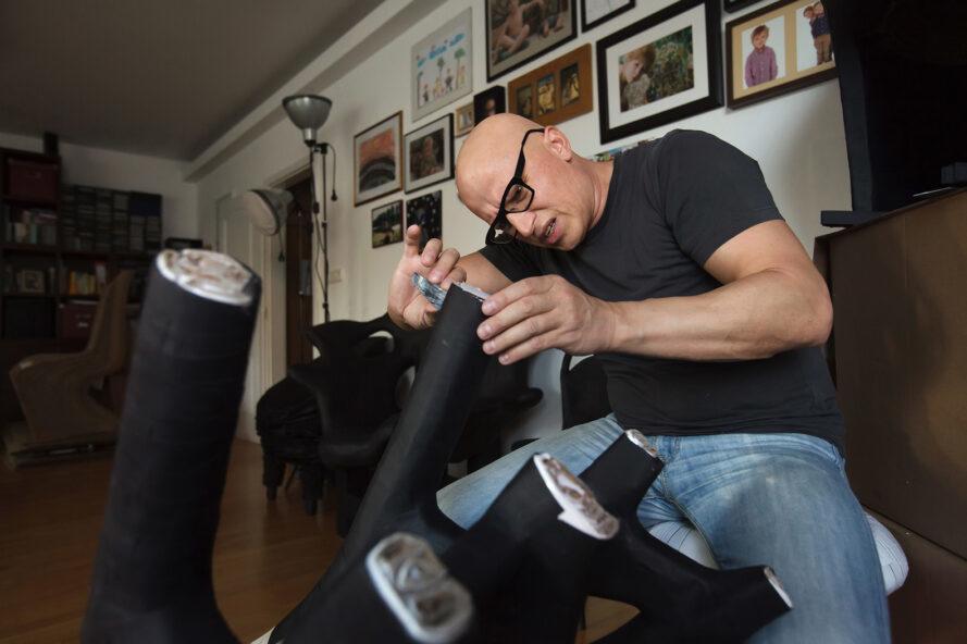 un homme assis et travaillant sur les jambes d'un meuble