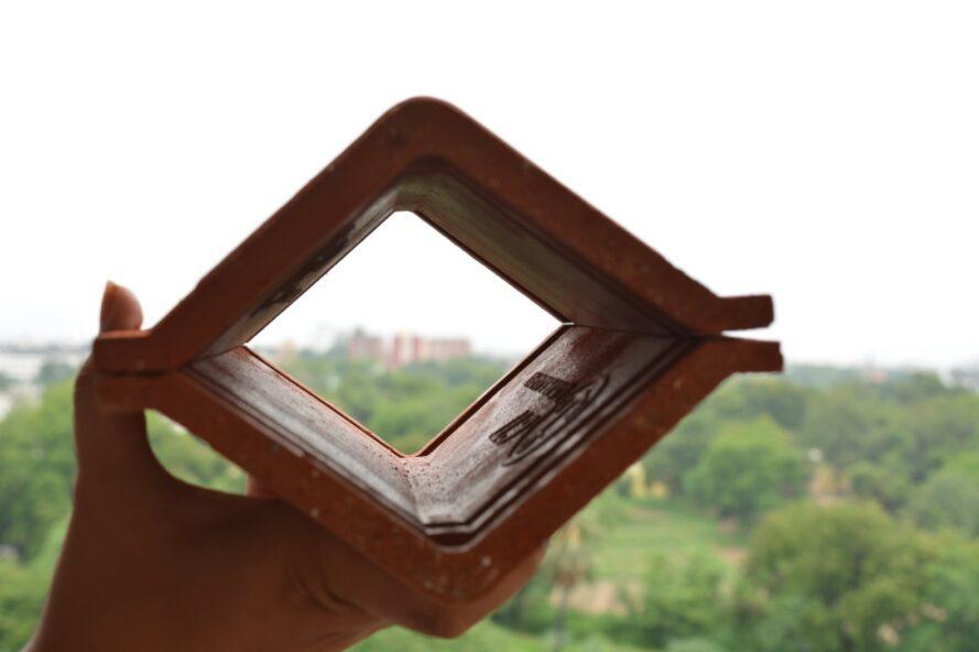 personne tenant deux carreaux d'argile en forme de V