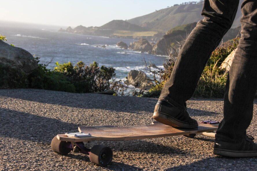 Gros plan du pied de l'homme sur une planche à roulettes en bois