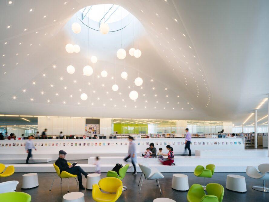 chaises vertes, blanches et jaunes sous un plafond sinueux avec une lucarne ronde
