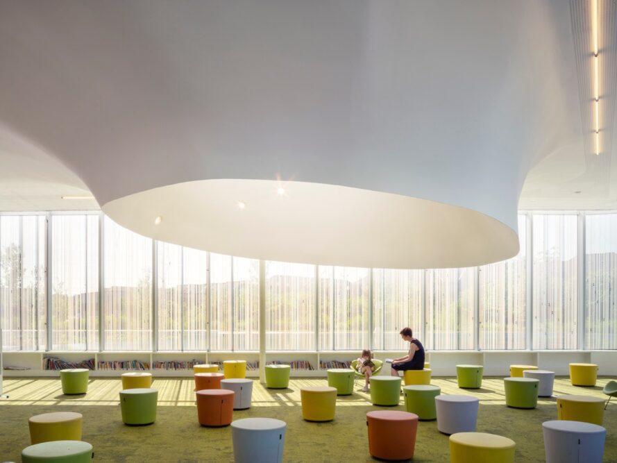 parent et enfant assis sur des tabourets colorés dans un bâtiment en verre