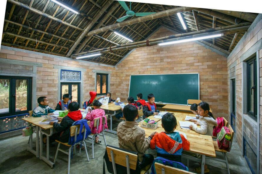étudiants à des bureaux en bois à l'intérieur d'une salle de classe avec des murs de briques