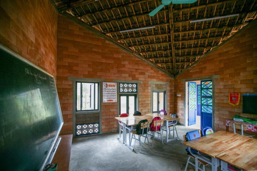 bureaux en bois vides dans la salle de classe avec des murs de briques